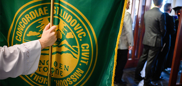 Hand holding pole of green banner at the Opening Service for the 183rd academic year with the installation of the Rev. Dr. Thomas J. Egger at Concordia Seminary, St. Louis.