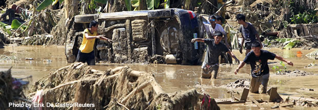 Residents wade in knee-deep mud in a subdivision hit by flash floods caused by Typhoon Washi in Iligan city in the southern Philippines island of Mindanao on Dec. 19, 2011.