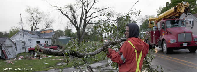 A member of a cleanup crew clears a branch in Thurman, Iowa, Sunday, April 15, 2012, after severe weather came through the area. A large part of the town in the western part of the state was destroyed Saturday night, possibly by a tornado, but no one was injured or killed. Fremont County Emergency Management Director Mike Crecelius said about 75 percent of the 250-person town was destroyed. (AP Photo/Nati Harnik)
